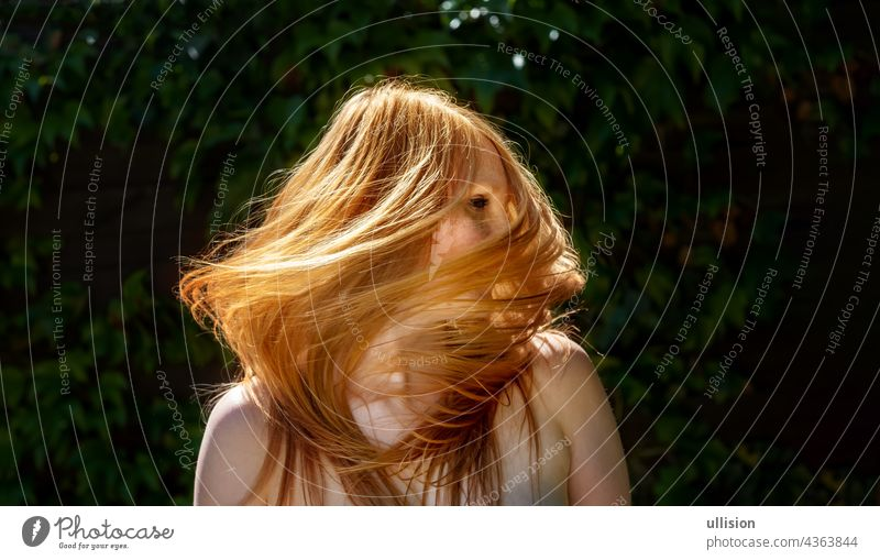 Sensual sexy portrait of beautiful redheaded woman shakes her hair outdoors with ivy background, copy space long stylish wavy sensual energy feminine freedom