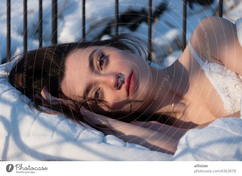 Portrait of an attractive, young, sexy, seductive woman in Bed, in white nightwear, head on hand Woman bed sleeping morning sun View dark brown pretty brunette
