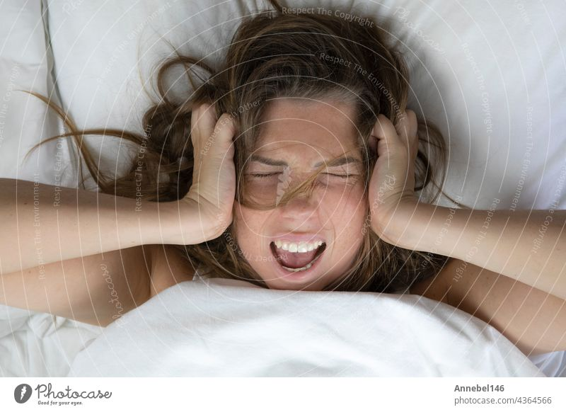 Young depressed unhappy woman lying in bed with health problems, screaming,hangover,depression,sleepless woman,migraine top view with white sheets insomnia