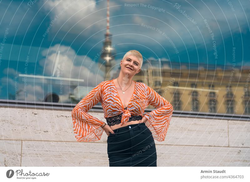 portrait of a young smiling woman with the berlin tv tower in the background studio confident outdoor window mirroring town city orange bustier blouse happy