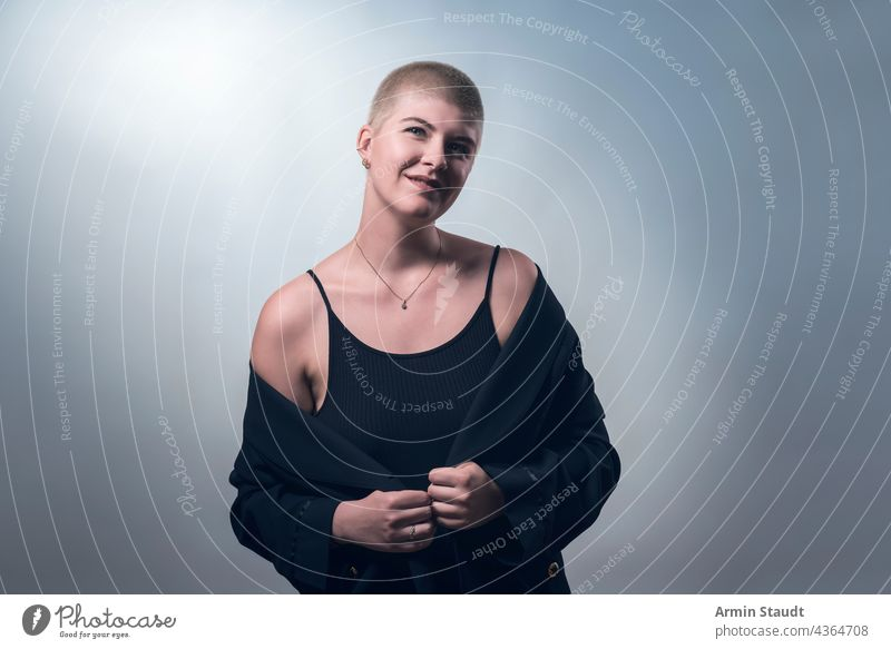 studio shot of a young, smiling woman with very short blonde hair in black clothes confident business smile shy timid lucky laugh piercing jewelry portrait