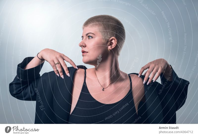 studio shot of a young, strong woman with very short blond hair in black clothes serious confident power powerful business piercing jewelry blonde portrait