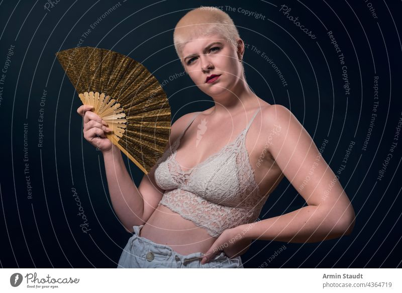 studio shot of a young, strong woman with very short blonde hair, a fan and a bustier serious confident power powerful business piercing jewelry portrait female