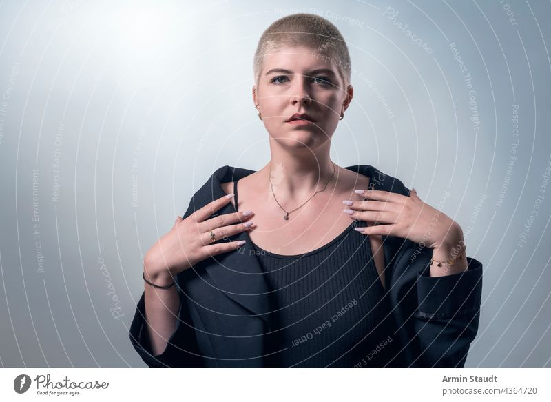 studio shot of a young, strong, beautiful woman with very short blond hair serious upright honest candid confident power powerful business piercing jewelry