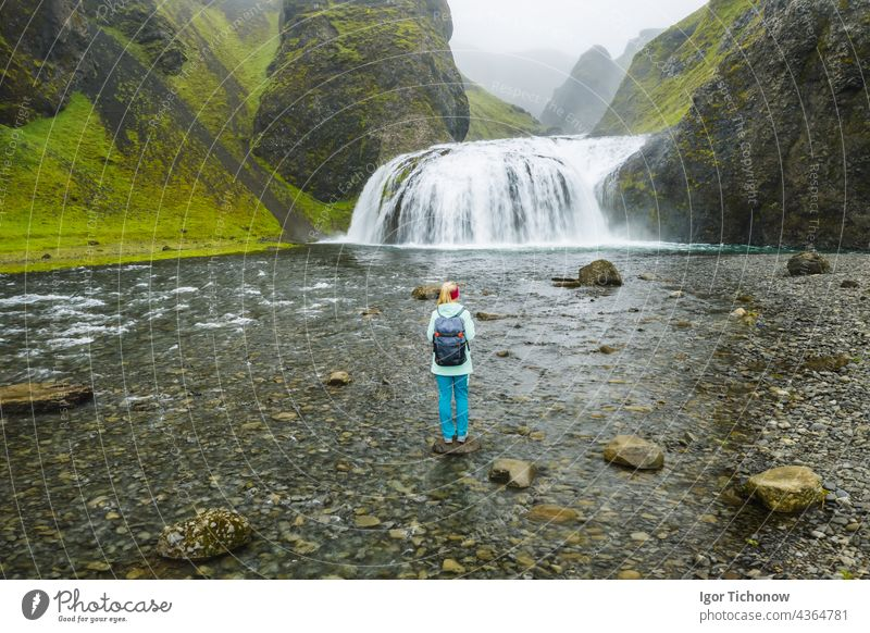 Aerial view of a hiker with backpack in front of the Stjornarfoss waterfall in South Iceland Waterfall Woman stjornarfoss Antenna Icelandic River Nature travel