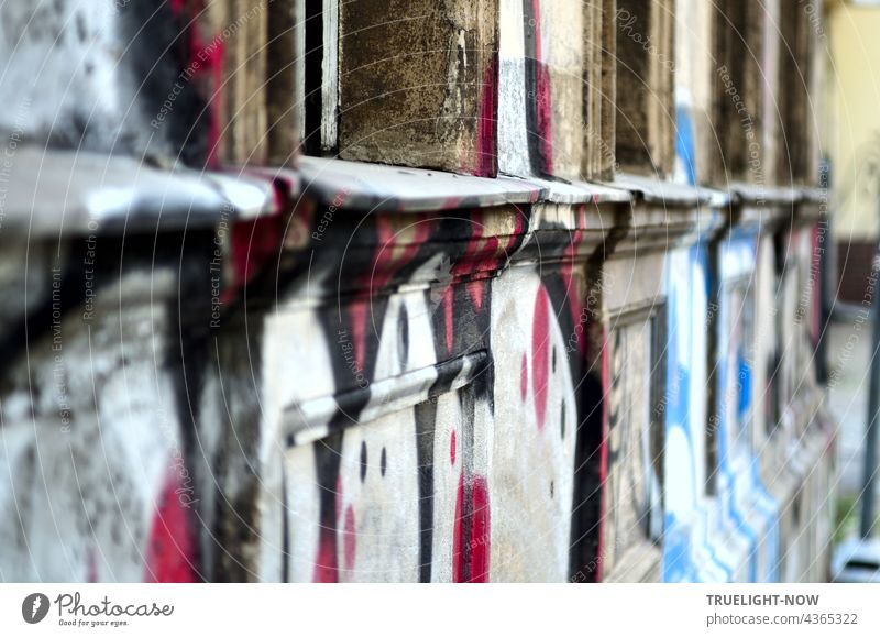Age meets youth: artfully graffitied dilapidated facade on the ground floor of an old house in Babelsberg, seen from the side at an acute angle. Facade