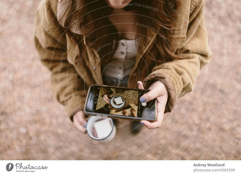 woman taking an overhead shot with her cell phone 18-25 20-25 autumn blue camping cheers community cook cookware culinary drinking hot chocolate enamel