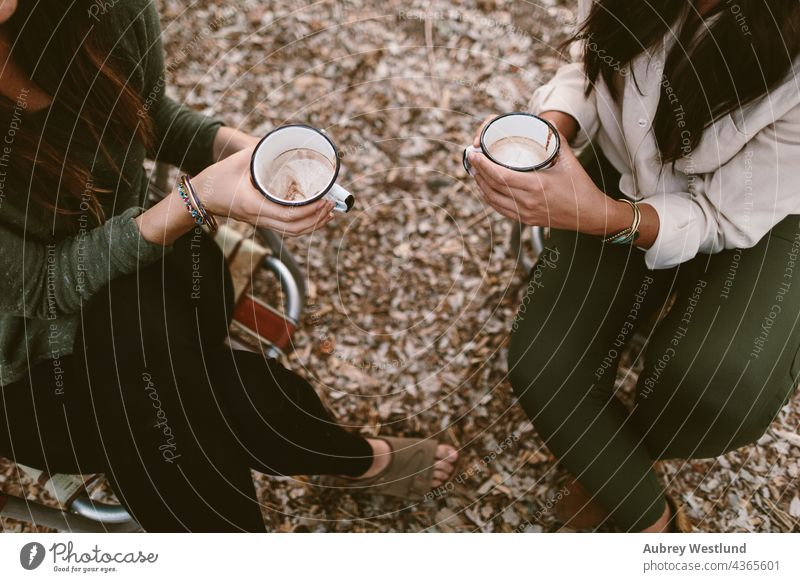 overhead shot of women holding thier hot chocolate in camping chairs 18-25 20-25 autumn blue cell phone cheers community cook cookware culinary