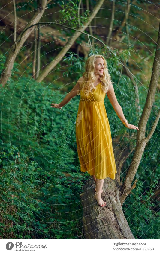 Carefree barefoot attractive blond woman balancing on an old fallen log in a forest wearing an elegant yellow dress looking away to the side with a happy friendly smile