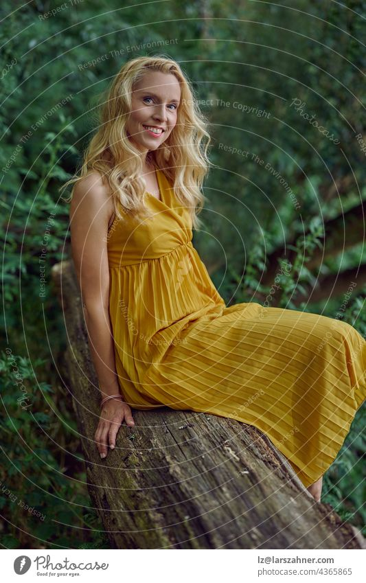 Attractive blond woman in a stylish yellow dress posing on an old tree trunk against greenery in summer looking at the camera with a smile in a close up portrait