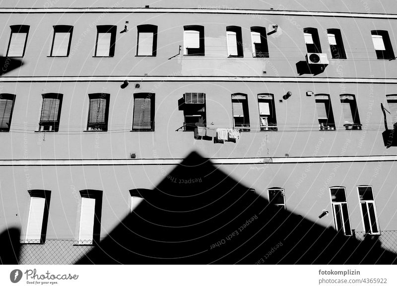 Shadow of a roof gable points to an open window with clothesline house wall Window Laundry Dry Wall (building) House (Residential Structure) Living or residing
