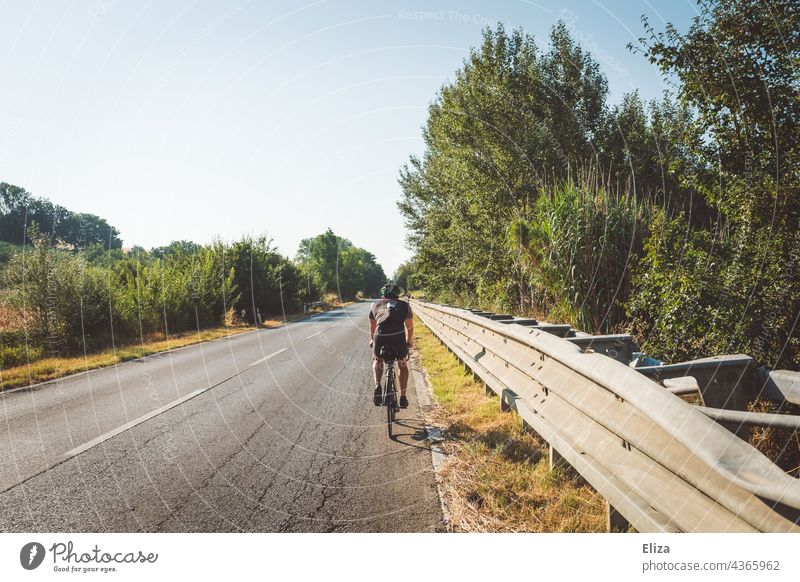 Racing cyclist in sportswear rides his bike on an Italian country road Racing cycle Road cyclist Sportswear Country road Italy Mediterranean Summer vacation