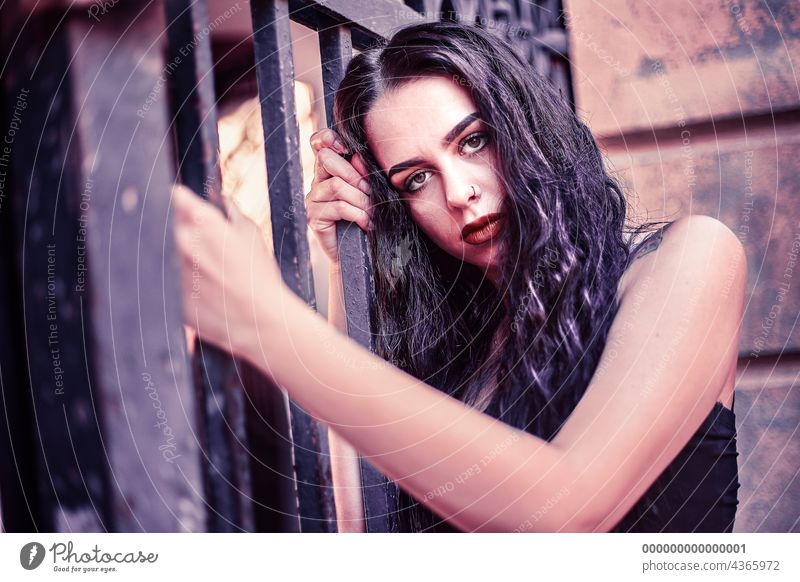 Sad girl portrait clinging to a gate urban sad woman young female beautiful fashion people person city street beauty lifestyle caucasian adult outdoor white