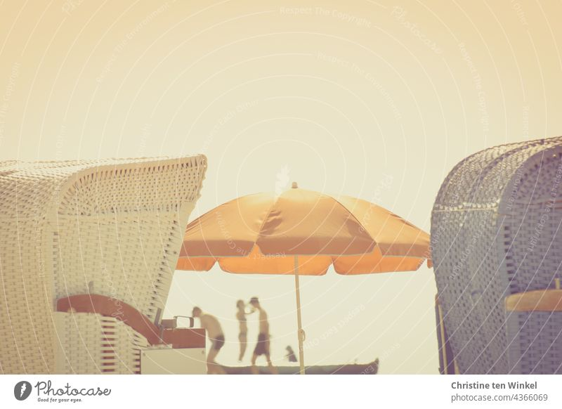 Spaces | on the beach ... Two beach chairs and in between an orange parasol and shadowy silhouettes of people in the back light Beach chair Summer Ocean