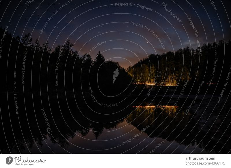 Night shot of calm water under starry sky with car lights in distance in forest Nature Exterior shot Deserted Landscape Lake Water stars Starry sky Starlit