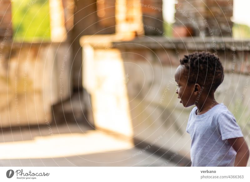 african boy playing in the patio child kid little childhood young fun people person happy game activity summer park sport football soccer afro home happiness