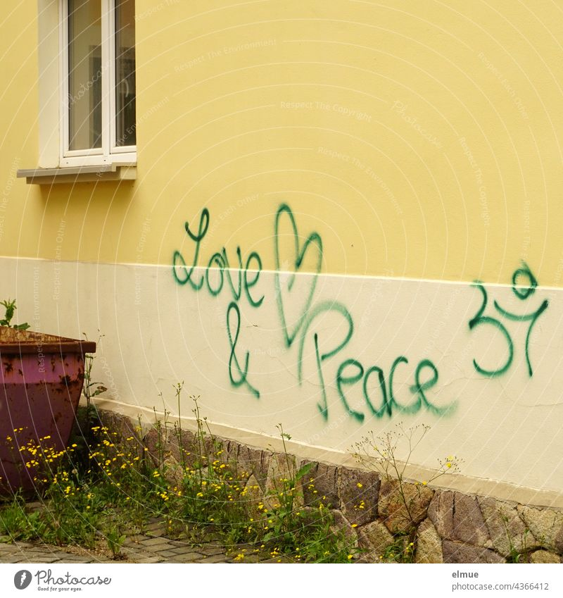 Love & Peace is written in green letters on a yellow house wall next to a parked container / graffito love and peace Graffito Graffiti Daub Container dwell