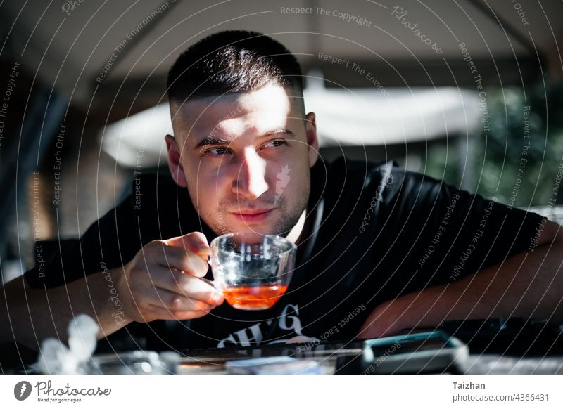 Close up of man drinking tea at   cafe person looking male sitting caucasian cheerful mug cup alone close up enjoyment fashionable fingers guy handsome heat