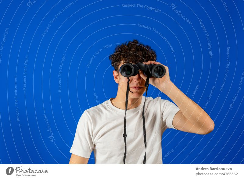 Young man over isolated blue background and looking in the distance with binoculars young hole humor model person photogenic portrait positive signs smile