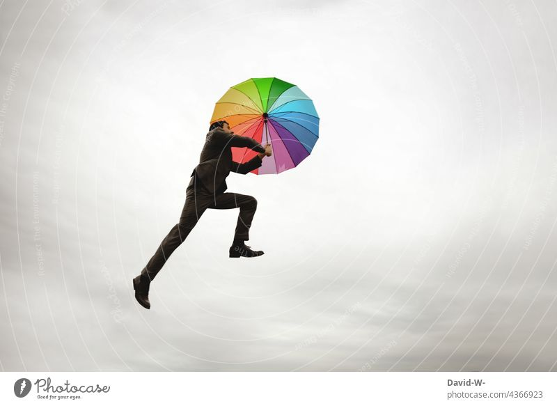 Man flies with the umbrella Freedom Flying Hover Umbrella Weightlessness variegated Sky Go up Ease Business suit-wearer Success concept