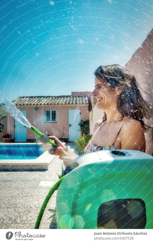 Pretty girl has fun throwing water with a hose. pretty wet splash house drops sunny season summer splashing refreshing happy laugh smile sexy home laughing