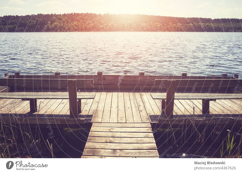 Wooden pier with benches at a lake against the sun, color toning applied. nature peaceful retro water wooden platform vacation tranquil scenic holiday relax