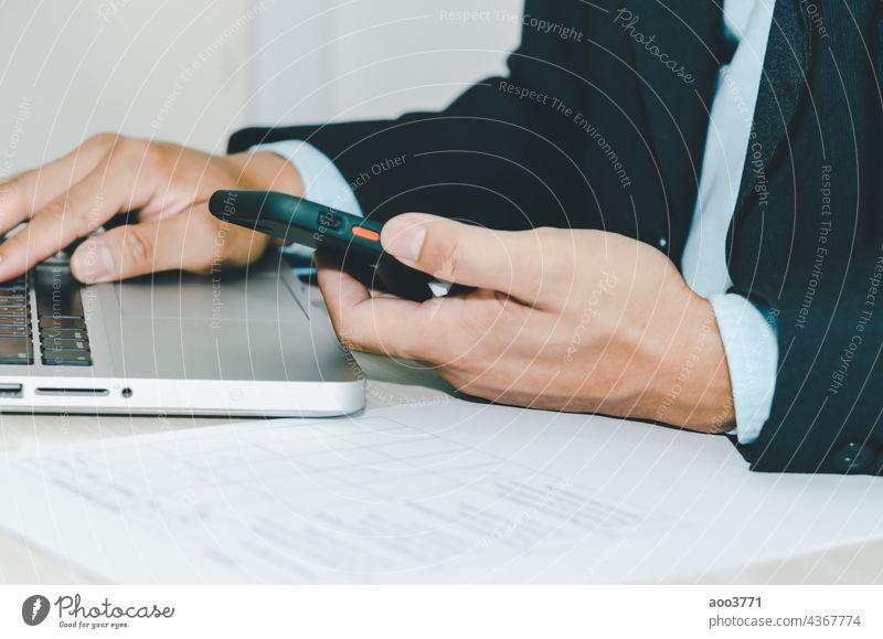 businessman holding smart phone and computer laptop. office technology people hand desk online person smartphone internet work marketing mobile use digital