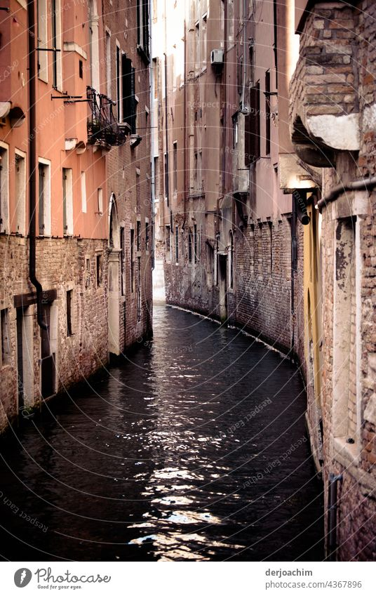 In a waterway of Venice. Old houses, not plastered, standing very close together. The water shimmers.  The sunlight penetrates the whole thing a little. The old shine of the houses has been lost for a long time.