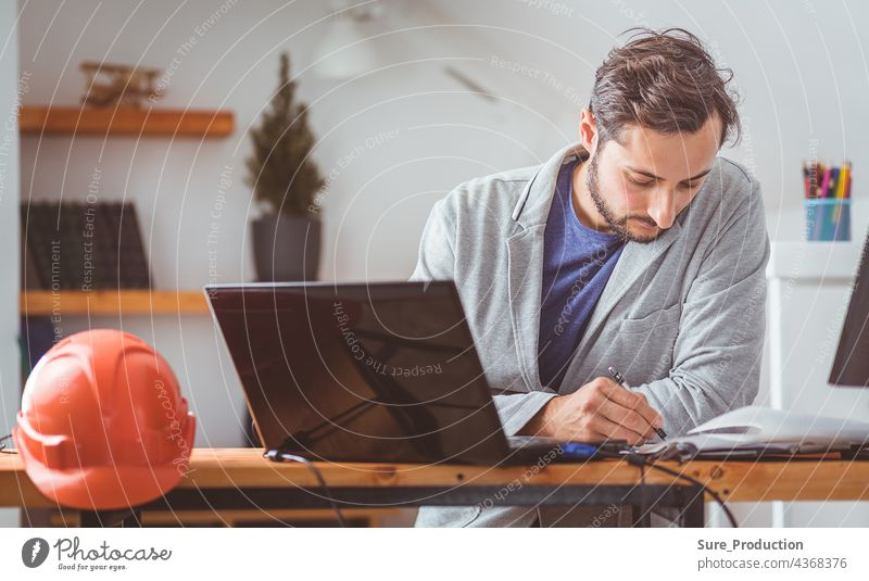 The designer thought and bowed his head while working with drawings and computers at the table on which the helmet lies. Color graded small business architect