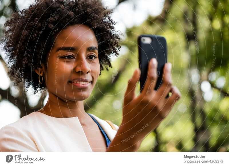 Afro business woman having a video call on mobile phone. afro app cellular talking communication outdoors software looking portrait wireless network person