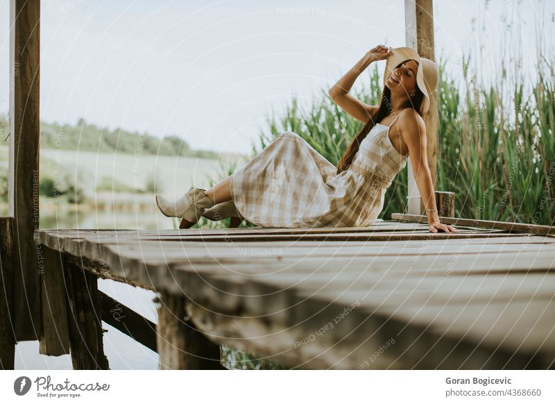Relaxing young woman on wooden pier at the lake beautiful concept enjoy summer nature caucasian good casual female sunny dream person vacation leisure rest