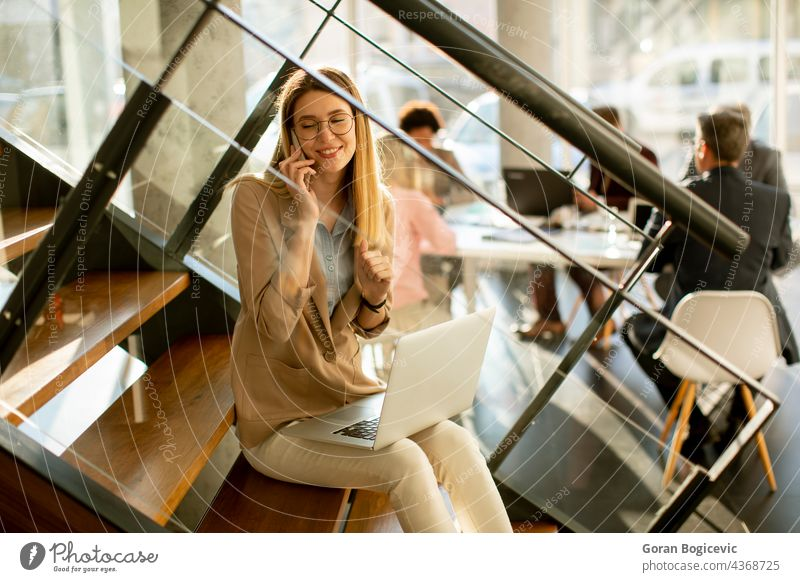 Young woman sitting on the stairs with laptop and using mobile phone in modern office in front of her team adult attractive beautiful business businesswomen