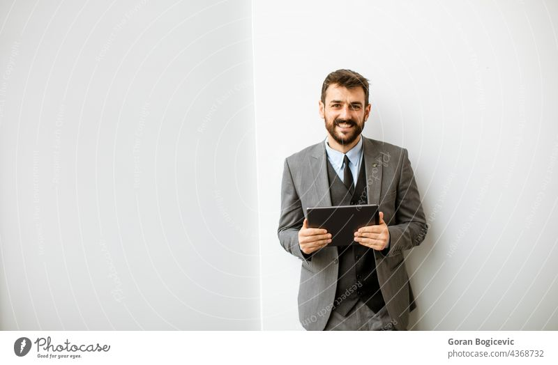 Young modern businessman using digital tablet in the office beard company corporate employee eyeglasses financial handsome indoors job leadership male manager