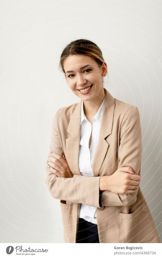 Young woman looking like a happy, proud and satisfied achiever, smiling with arms crossed against white wall beauty young beautiful casual female portrait