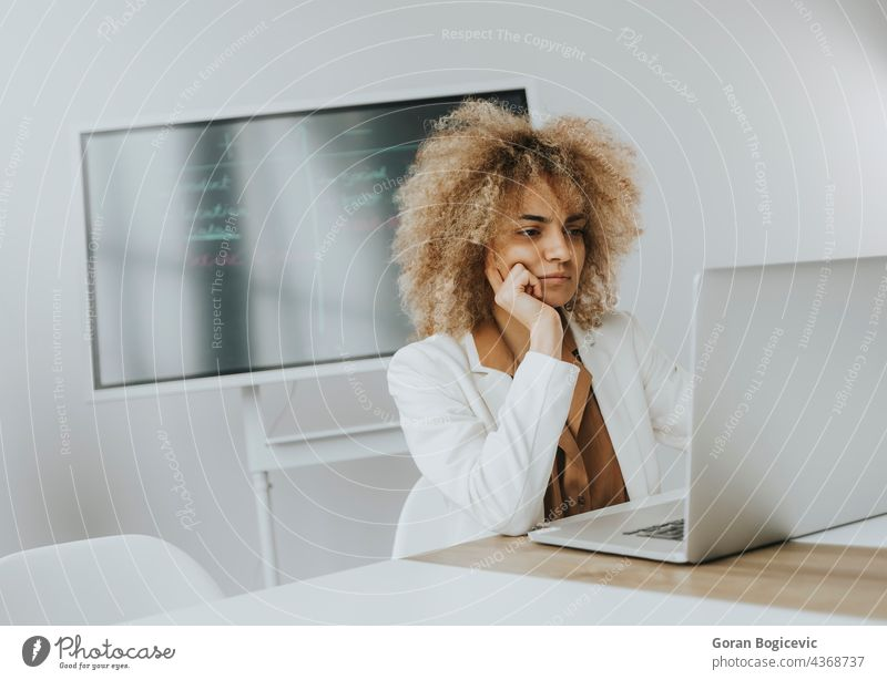 Young curly hair woman working on laptop in bright office with big screen behind her adult attractive beautiful black business caucasian communication computer