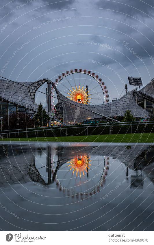 Ferris wheel at night in the Olympiapark Munich Ferris wheel ride Night Evening funfair Fairs & Carnivals Lighting Rain Wet Puddle reflection
