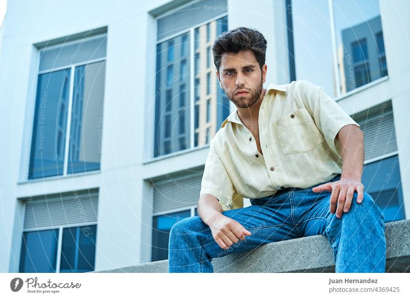 man posing in front of a building with large windows young men university college campus education guy school student study studying outside handsome horizontal