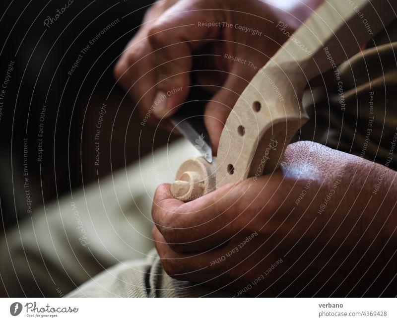 Violin maker artisan senior hands usign a knife to carve a Stradivarius model violin head and scroll luthier viola violinmaking carving wood sculpting cremona