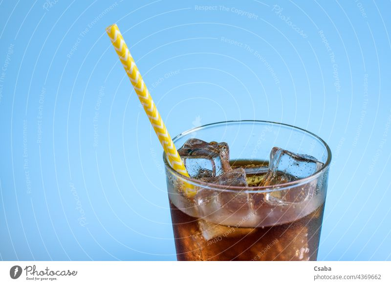 A glass of cola with ice on a blue background Cola Soda Soda Glass Soft Drinking Ice Cold Straw Summer Refreshment Caffeine Liquid Blue Brown Beverage