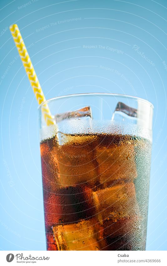 A glass of cola with ice on blue and pink background soda soft drink cold straw summer refreshment caffeine liquid brown beverage condensation dew cube