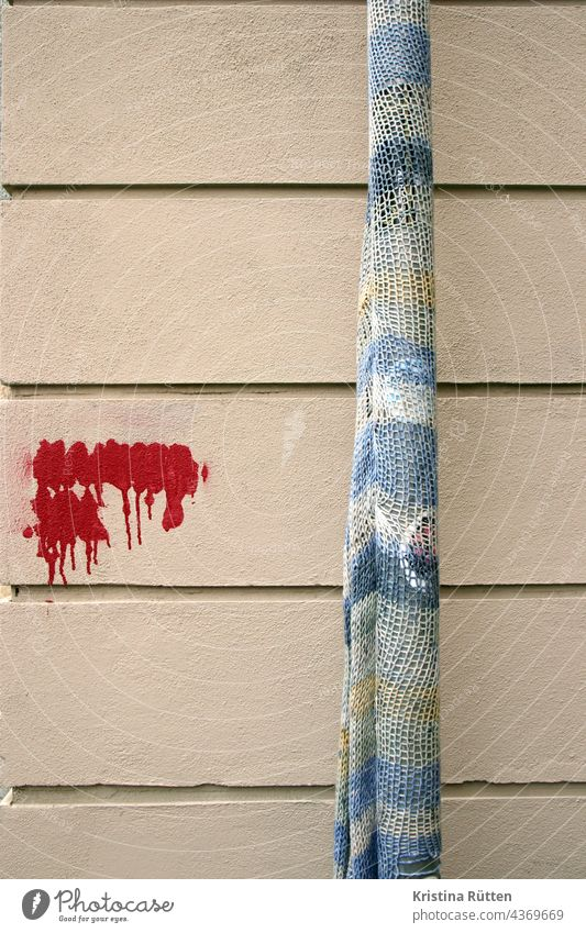rain tube with rope and painted over graffiti guerilla crickets Guerilla Knit urban knitting yarn bombing Downpipe street art out Public Knitted embroidered