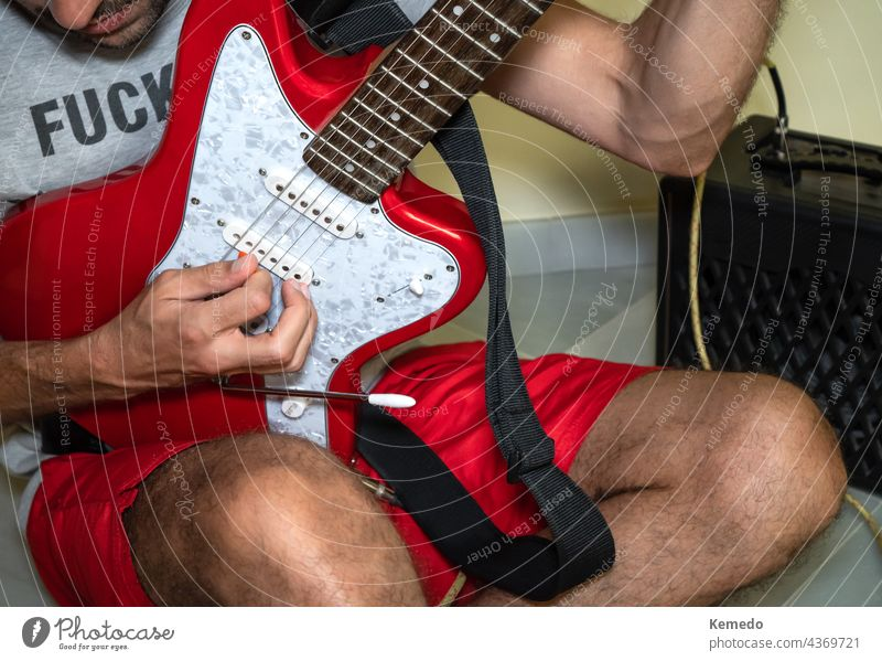 Unrecognized man sitting on the floor playing a red electric guitar. guitarist person rude male rock punk casual alternative musician player lifestyle grunge