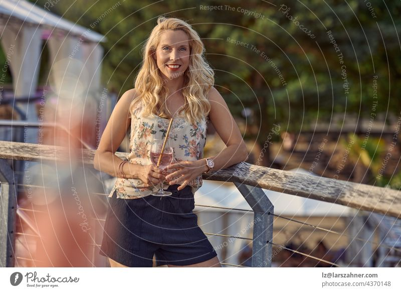 Pretty relaxed blond woman enjoying a tropical cocktail on summer vacation standing leaning on wooden railings looking at the camera with a friendly smile and copyspace