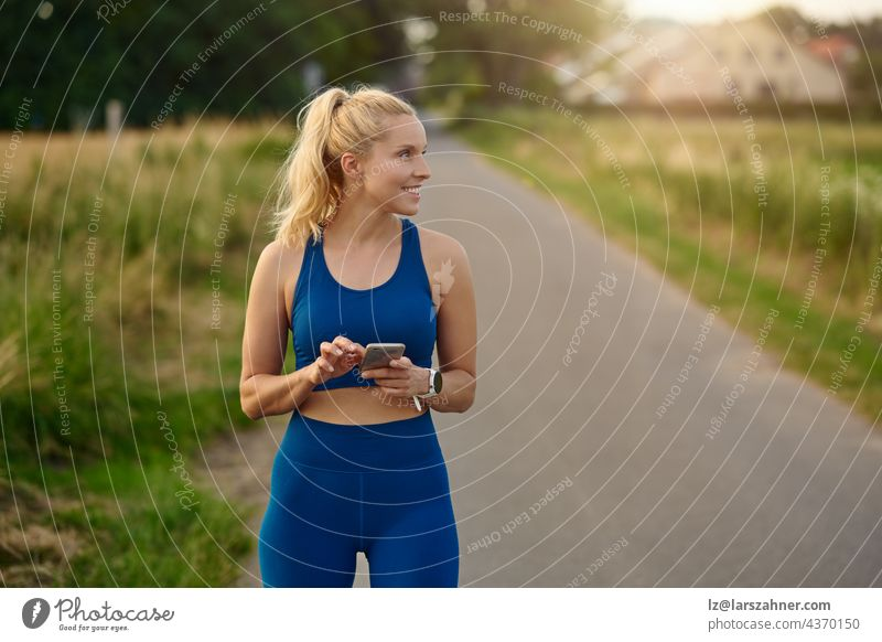 Fit athletic woman pausing to consult her mobile phone while out jogging on a rural footpath looking to the side with a happy smile of satisfaction and pleasure