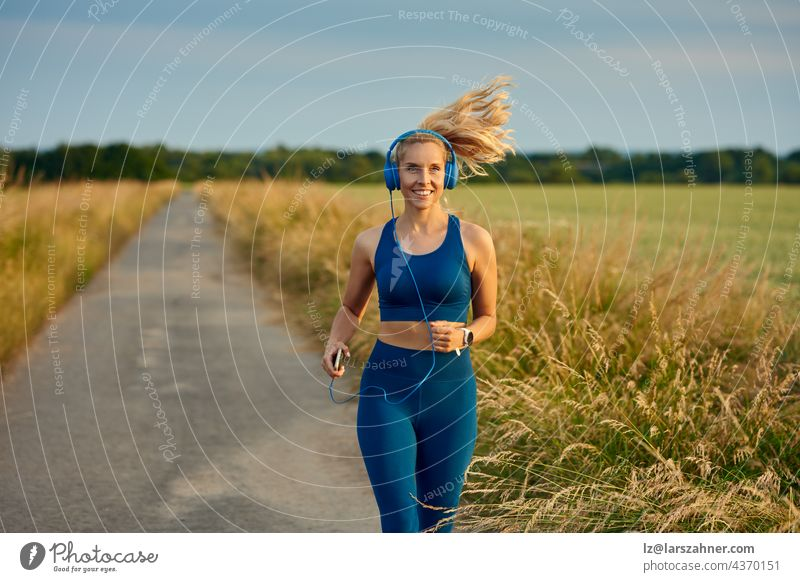 Fit vivacious young woman jogging along a footpath in open fields approaching the camera with a happy smile and ponytail flying out behind in a healthy active lifestyle concept