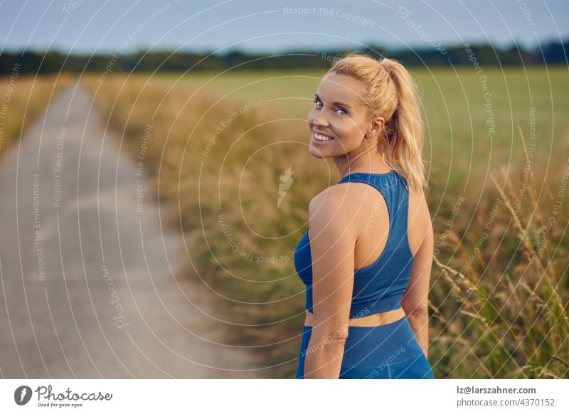 Attractive fit healthy woman turning to smile at the camera as she prepares to work out jogging along a rural footpath in a healthy active outdoor lifestyle concept