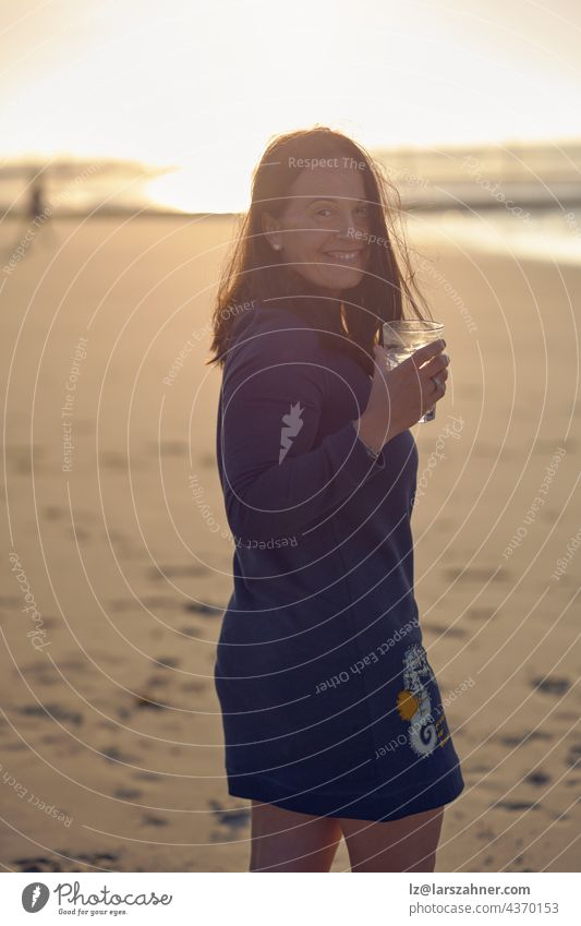 Woman enjoying sunset on a tropical beach while drinking a cocktail turning to look over her shoulder at the camera with a happy vivacious smile woman brunette