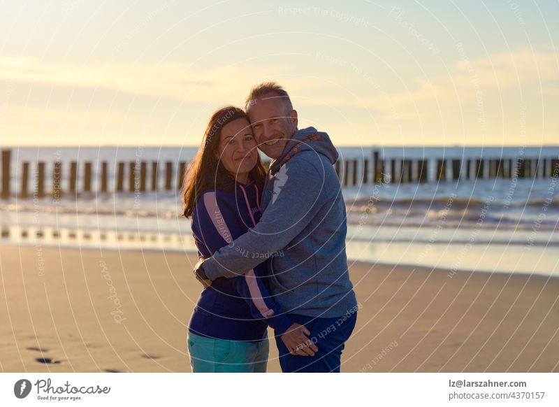 Happy romantic middle-aged couple enjoying a loving cuddle on a deserted tropical beach at sunset standing in a close embrace smiling at the camera with copy space