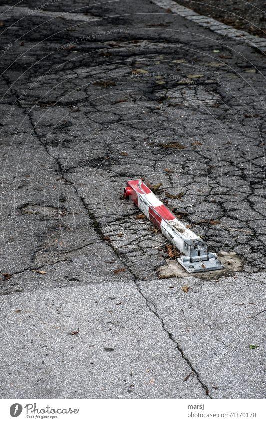 Parking lockout, overridden. Asphalt brittle Old corrupted Parking lot off Loneliness Street Red-white-red