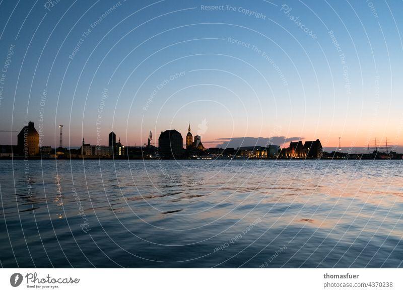 Silhouette of port city at sunset Back-light Moody Twilight Evening Sunset Light (Natural Phenomenon) Horizon tranquillity travel Summer Sky coast bank Ocean